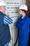 Female apprentice electrician checking fuse box. Female stock images