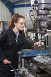 Female Apprentice Engineer Working On Drill In Factory. Female Apprentice Engineer Working With Drill In Factory royalty free stock photos