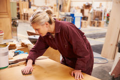 Female Apprentice Finishing Wood In Carpentry Workshop Royalty Free Stock Photos