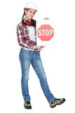 Female apprentice holding stop sign. Confident female apprentice holding stop sign Royalty Free Stock Photo