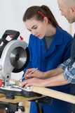 Female apprentice learning to use circular saw. Circular royalty free stock images