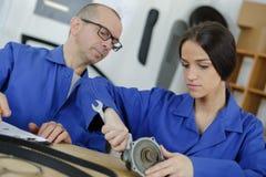 Female apprentice mechanic manipulating car part with teacher. Apprentice Stock Image