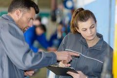 Female apprentice in overalls holding clipboard. Female apprentice in overalls holding a clipboard stock photos