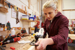 Female Apprentice Planing Wood In Carpentry Workshop Royalty Free Stock Photo