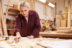 Female Apprentice Planing Wood In Carpentry Workshop Royalty Free Stock Image