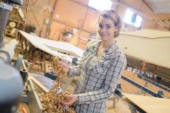 Female apprentice planing wood in carpentry workshop. Shaving stock photo