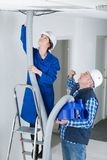 Female apprentice in suspended ceilings. Female royalty free stock photo