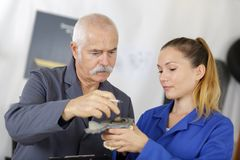 Female apprentice using drill in factory. Female royalty free stock image