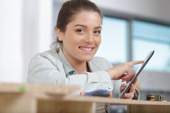 Female apprentice using tablet in furniture workshop. Female apprentice using a tablet in furniture workshop royalty free stock photography