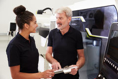Female Apprentice Working With Engineer On CNC Machinery Royalty Free Stock Photo