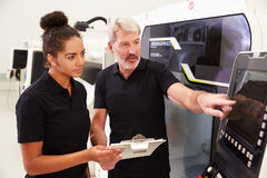 Female Apprentice Working With Engineer On CNC Machinery Royalty Free Stock Photos