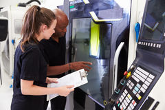 Female Apprentice Working With Engineer On CNC Machinery royalty free stock photography