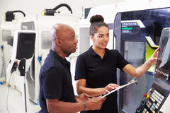 Female Apprentice Working With Engineer On CNC Machinery Royalty Free Stock Image
