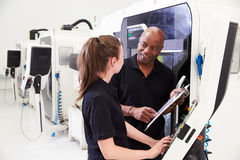 Female Apprentice Working With Engineer On CNC Machinery stock photography
