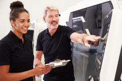 Female Apprentice Working With Engineer On CNC Machinery Stock Image