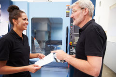 Female Apprentice Working With Engineer On CNC Machinery Royalty Free Stock Images