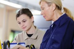 Female apprentice working with mentor. Woman royalty free stock image