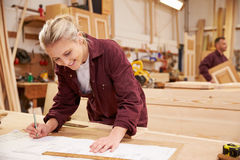 Female Apprentice Working With Plans In Carpentry Workshop Stock Photos
