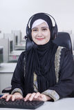 Female Arabian operator with headphones. Portrait of a pretty female Arabian operator working in the office with headphone and wearing islamic clothes Stock Photos