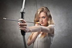 Female archer. Young woman drawing a bow Royalty Free Stock Photography