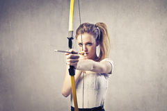 Female archer. Young woman drawing a bow Stock Photo