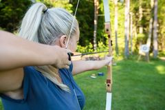 Female Archer Aiming Arrow At Target Board In Forest Royalty Free Stock Images
