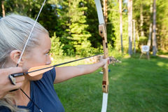 Female Archer Aiming Arrow At Target Board In Forest Stock Photo