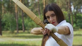 Female archer aiming her bow on target stock video