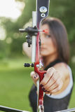 Female Archer. Front View Of Female Archer Training At The Range. Focus Is On Bow And Arrow Royalty Free Stock Images