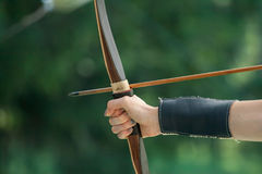 Female archer hand keeping bow. Aiming arrow to the target Stock Photography