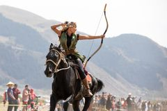 Female archer shooting an arrow on horseback. Royalty Free Stock Photography