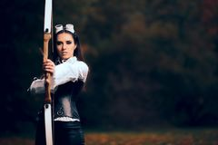 Female Archer Warrior in Costume with Bow and Arrow. Steampunk warrior princess hunting in nature Royalty Free Stock Image