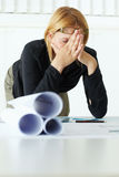 Female architect. Mid adult architect with hands over face, having headache. Copy space Royalty Free Stock Photos