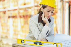 Female architect. Mid adult architect examining blueprints and smiling. Copy space Stock Images