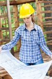 Female Architect Analyzing Blueprint In Wooden Stock Photo