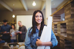 Female architect with blueprints while colleagues in background Royalty Free Stock Photo