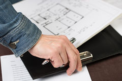 Female Architect clips some floorplans to a clipboard. Royalty Free Stock Photography