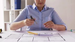 Female architect with compass measuring blueprint stock video