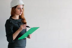 Female architect at the construction site with drawings and note Royalty Free Stock Photography