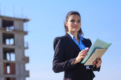 Female architect at a construction site. Young female architect working at construction site Stock Images