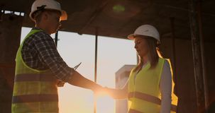 Female architect and construction worker shaking hands. Low angle view, copy space. Female architect and construction worker shaking hands. Low angle view, copy stock footage