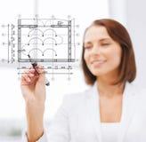 Female architect drawing blueprint Stock Images
