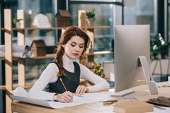 Female architect drawing building plan at workplace. With computer royalty free stock photography