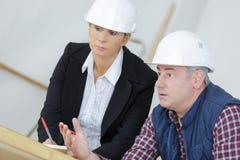 Female architect and foreman examining blueprints Stock Photo