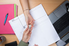 Female architect hand, handing over house key to a customer. Royalty Free Stock Images