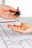 Female architect hand,handing over house key to a customer. Royalty Free Stock Images
