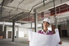 Female Architect In Hardhat With Blueprints At Site Royalty Free Stock Photography