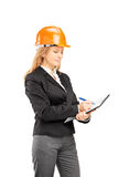 Female architect with a helmet writing on a clipboard Royalty Free Stock Photos