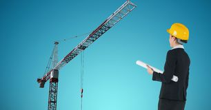 Female architect holding blue prints while looking at crane. Digital composite of Female architect holding blue prints while looking at crane Stock Image