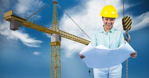 Female architect holding blueprint against crane Royalty Free Stock Image
